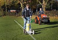 BLOEMENDAAL - Hockey op ECHT gras. Jules Hustinx, Clubmanager van HC Bloemendaal trekt de lijnen. Hidde Maas maait  het gras. COPYRIGHT KOEN SUYK