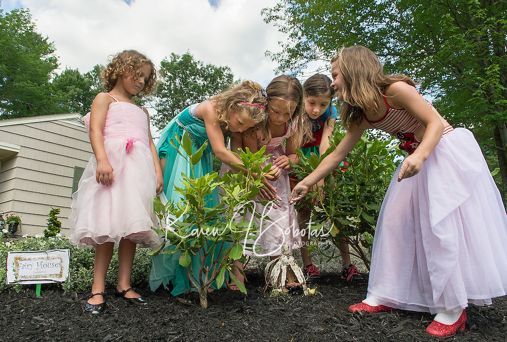 """Boys and Girls Clubs' """"Fairies"""" Hannah, Elizabeth, Madi, Reese and Kimmy made a special appearance at Robert King and Elaine Muller's home Friday afternoon to add sparkle to their fairy houses displayed among the gardens that will be part of Opechee Garden Club's annual """"Awesome Blossoms""""  Garden Tour on Saturday.   (Karen Bobotas/for the Laconia Daily Sun)"""