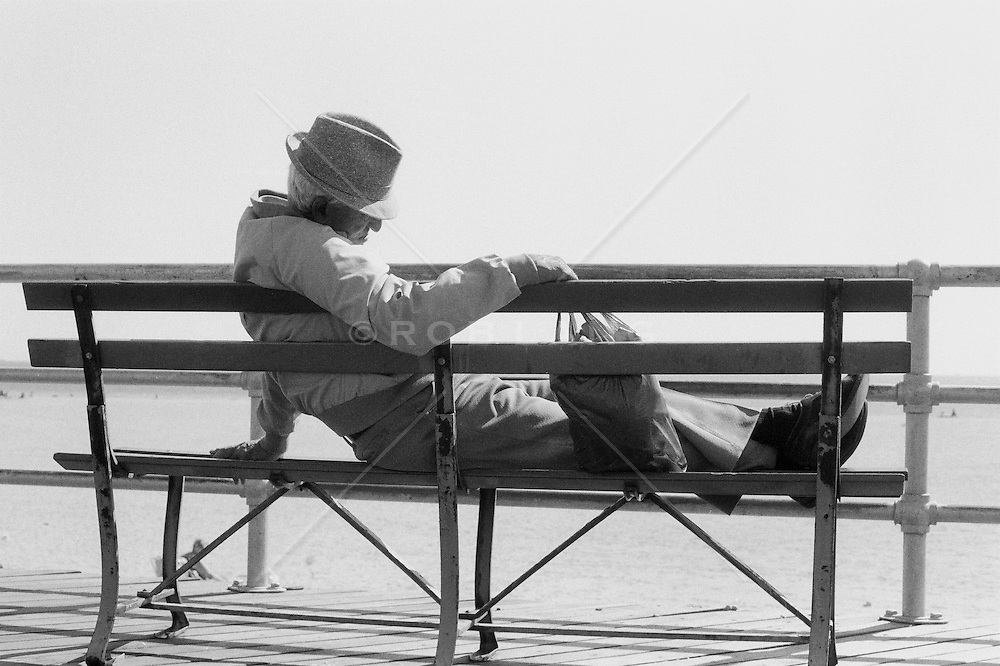 Elderly man resting on a bench in Coney Island, NY