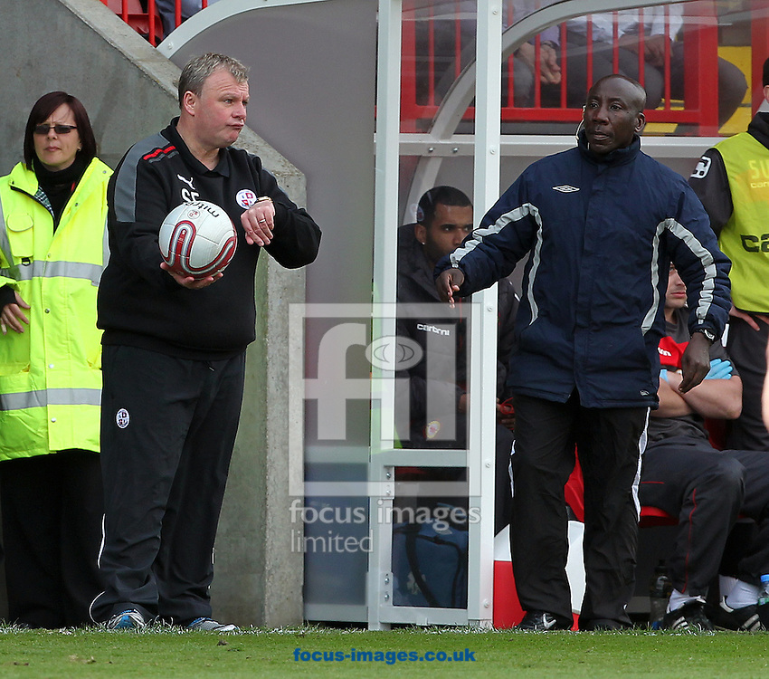 Picture by Paul Terry/Focus Images Ltd. 07545642257.06/04/12.Steve Evans (L) , Manager of Crawley Town sarcastically hold on to the ball before fourth official, Dave Bushell,  gets the ball back into play during the Npower League 2 match at Broadfield stadium, Crawley, West Sussex.