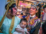 08 FEBRUARY 2013 - BANGKOK, THAILAND: Chinese opera performers hold their baby back stage before performing for Chinese New Year at Seacon Square in Bangkok. Chinese opera is popular in Thailand and is usually performed in the Teochew language. The weeks surrounding Chinese New Year are important for retailers in Thailand and many malls put on special promotions and events honoring Chinese culture, like Lion Dances or Chinese Opera. Thailand has a large Thai-Chinese population. Millions of Chinese emigrated to Thailand (then Siam) in the 18th and 19th centuries and brought their cultural practices with them.    PHOTO BY JACK KURTZ