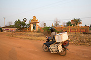 A motorbike passes the village temple on a street in the village of in Banteay Char, near Battambang, Cambodia.