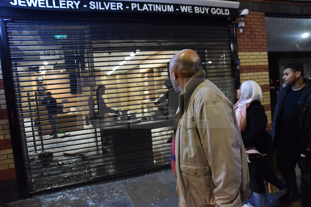 © Licensed to London News Pictures. 25/10/2019. London, UK. Passers by look on as shopkeepers clean up after a jewellers on Uxbridge Road was ram-raided buy three men in a black Rangerover in Shepherds Bush. Members of the public wrestled one of the robbers to the ground as who was apprehended by police in under a minute. The other two escaped on foot.  Photo credit: Guilhem Baker/LNP