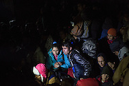 Asylum seekers sit on the ground after being instructed by Greek police to wait their turn to cross the border into Macedonia on the night of December 3, 2015.