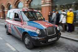 © licensed to London News Pictures. London, UK 23/11/2012. A London black cab goes past whilst workers of London Taxi Company, which makes black cabs, staging a protest outside St Pancras Station in London as part of a campaign to save jobs after 156 workers lost their jobs. Photo credit: Tolga Akmen/LNP