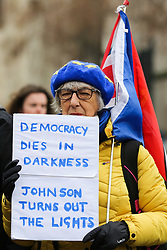 © Licensed to London News Pictures. 22/01/2020. London, UK. A Pro-European protester holds a sign 'DEMOCRACY DIES IN DARKNESS JOHNSON TURNS OUT THE LIGHTS' as anti-Brexit campaigners demonstrate outside Houses of Parliament with nine days to  Brexit Day. Photo credit: Dinendra Haria/LNP