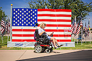 10 SEPTEMBER 2012 - TEMPE, AZ:      A woman drives her electric wheelchair past an American flag made of Legos in  the Healing Field in Tempe, AZ, Monday. The Exchange Club of Tempe and the city of Tempe are hosting the 9th Annual Healing Field display. The annual event posts three thousand American flags in the Tempe Beach Park. The flags are 3?X5?  and stand 8? tall. The display is a tribute to those who died in the terrorist attacks of September 11, 2001. Nearly 3,000 people were killed when terrorists affiliated Al-Qaeda crashed commercial airliners into the World Trade Center in New York, the Pentagon in Arlington, VA, and a field in Ohio.   PHOTO BY JACK KURTZ