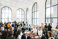"""ROME, ITALY - 15 OCTOBER 2018: A view of the showroom with FENDI artisans explaining the productions process of FENDI items to students during the LVMH Journées Particulières exhibition at the Fendi headquarters in Rome, Italy, on October 15th 2018.<br /> <br /> The LVMH Journées Particulières is is a series of exhibitions that show the creations and history of the LVMH fashion houses. The driving theme behind the Journées Particulières is to allow the general public to discover the inner workings of the Houses which are part of the LVMH heritage.The LVMH Journées Particulières exhibition by fashion house FENDI takes place at their headquarters at the Palazzo della Civiltà Italiana, also called the """"Colosseo Quadrato"""" (Square Colosseum),  an outstanding jewel of the 20th century Roman architecture."""