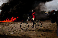 A boy rides by a massive gasoline fire in Malakal the capital of Upper Nile State which is home to vast oil wealth.