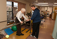PTA Anthony Reeder goes through mobility exercises with Dorothy Moore on the bar at Belknap County Nursing Home Tuesday afternoon.  (Karen Bobotas/for the Laconia Daily Sun)