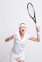 Young female tennis player with racket cheering against white background
