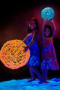 Two young girls with large glowing twig balls stand on a glowing tarp.Black light