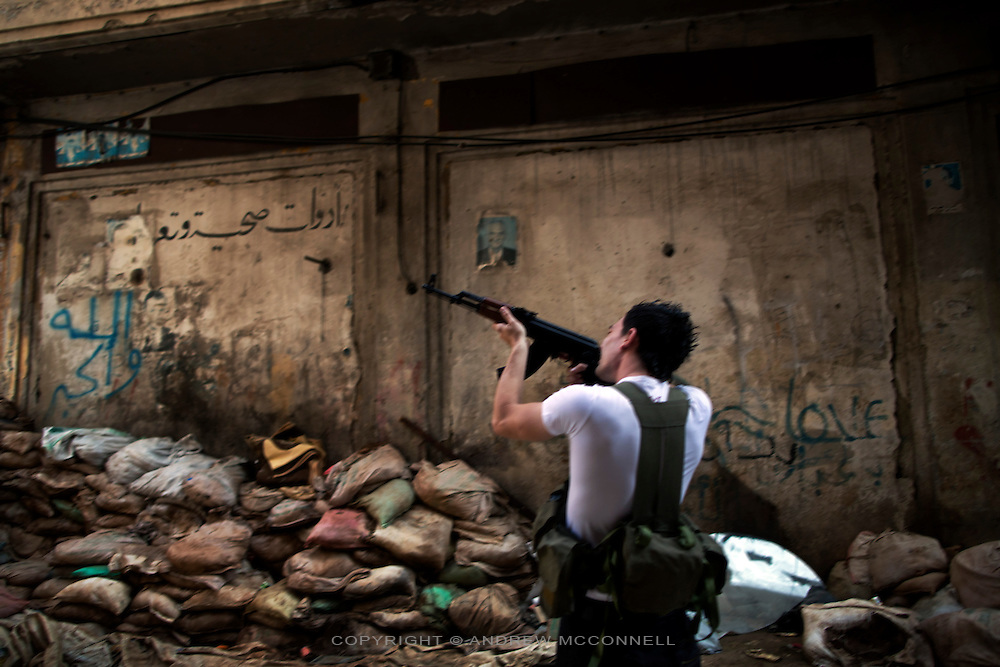 A Sunni fighter aims his weapon during heavy clashes between Sunni muslim and Alawite muslim factions, in Bab al-Tabbaneh, Tripoli, Lebanon. Bab al-Tabbaneh is a Sunni neighbourhood situated below the hilltop district of Jabel Moshen, which is home to the majority of Lebanon's Alawite muslim community. Over the past two years the area has seen regular clashes in which scores of people have been killed and hundreds wounded. The fighting is directly linked to the civil war in Syria and there are fears that it will spread to other towns and cities in Lebanon.