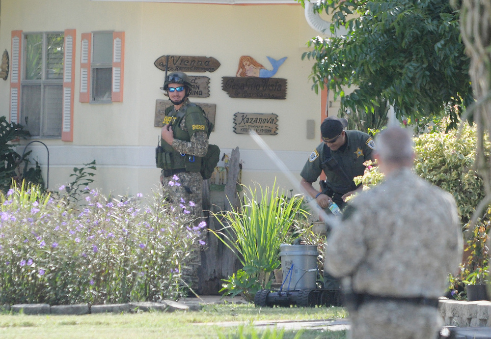 Andrew Knapp, FLORIDA TODAY -- Oct. 20, 2011 -- SWAT team members pick up bottles of water from a remote-control robot Thursday during a standoff with a resident on Barr Street on Merritt Island.