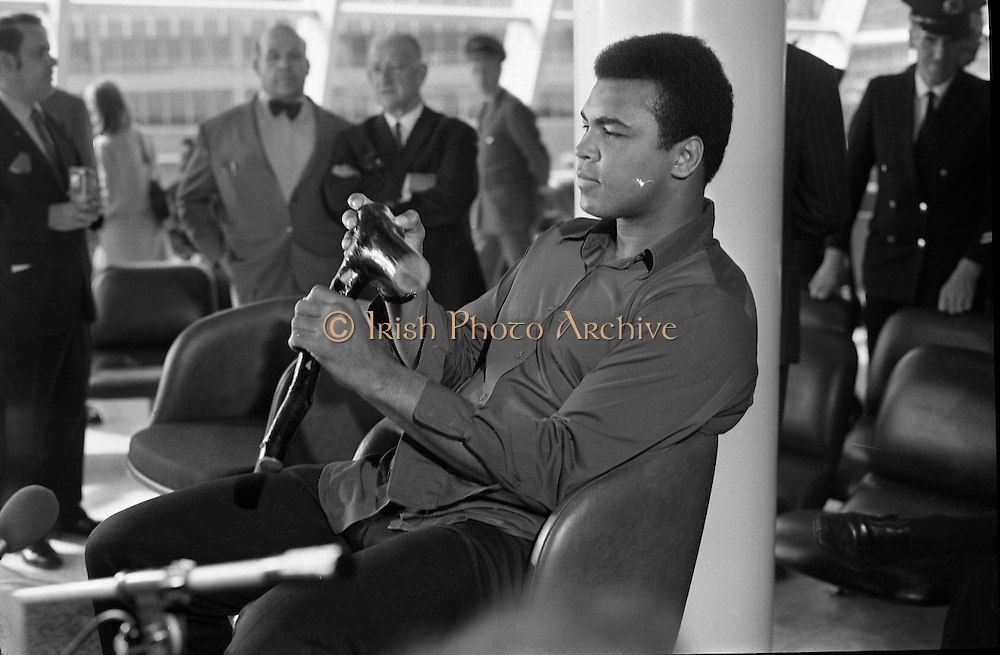 Muhammad Ali In Dublin..1972..11.07.1972..07.11.1972..11th July 1972..Prior to his fight against Al 'Blue' Lewis at Croke Park, Dublin, former World Heavyweight Champion Muhammad Ali arrives at Dublin Airport..The fight was part of his build up for for a championship fight against the current World Champion, 'Smokin'  Joe Frazier. Ali had been stripped of the title partly due to his refusal to join the American military during The Vietnam War,which he had opposed...Image of Muhammad Ali as he examines a shillelagh which was presented to him on his arrival in Dublin.