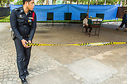 03 MARCH 2013 - BANGKOK, THAILAND: <br />  A Thai policeman puts perimeter tape around a polling place in Benchasiri Park in Bangkok. Bangkok residents went to the polls Sunday to elect a new governor. Voter turnout was expected to be heavy for a local election. Pongsapat Pongchareon, the Pheu Thai candidate is thought to hold a slight lead over Sukhumbhand Paribatra, the Democrats' candidate. There are a total of 25 candidates in the election but only Pheu Thai and the Democrats are given a chance of winning.    PHOTO BY JACK KURTZ
