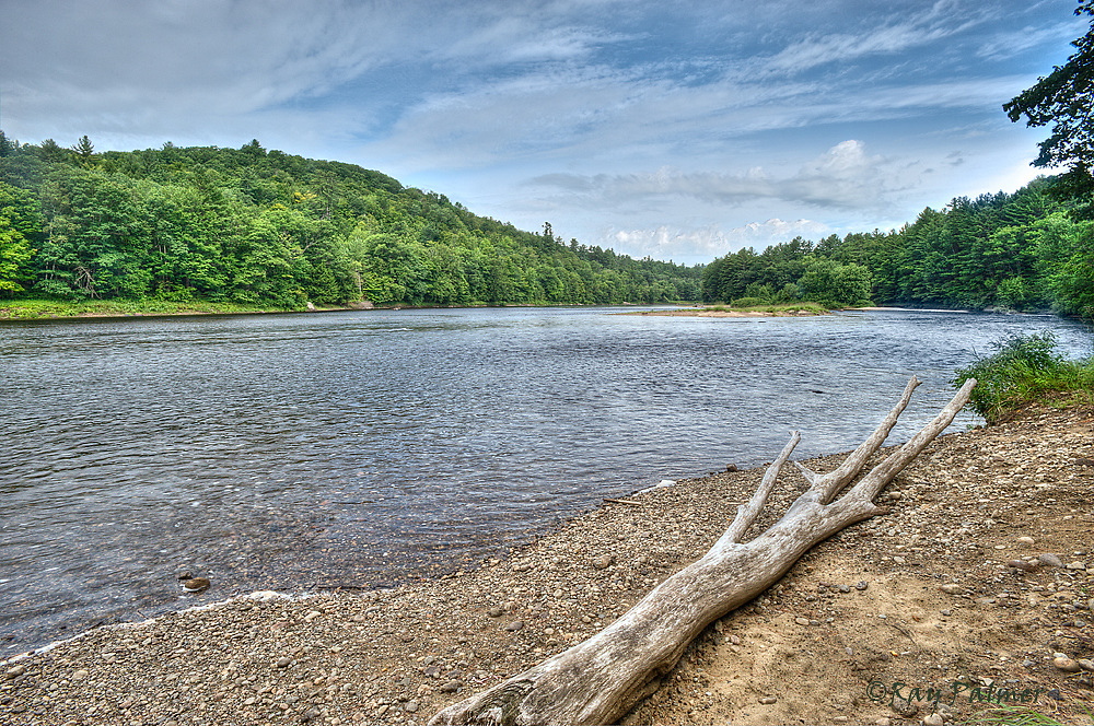 Hudson River Recreation Area, Adirondacks, NY<br /> _RP17169_7012_HDR.<br /> Not quite stormy, gray clouds skudded across parts of the sky under a blue dome above.  From Thurman, the Hudson is slow, broad water, broken occasionally by riffles and small islands in the stream.  Flotillas of inner tube enthusiasts are common up here, as are the usual canoes and kayaks.   The embankment I climbed down to get her was scooped out and unstable, a clue, along with the denuded trunk, that the river is not always so placid.  But today I'm content to take this temporary seat at the river's edge and enjoy summer's peak in this part of the Adirondacks.