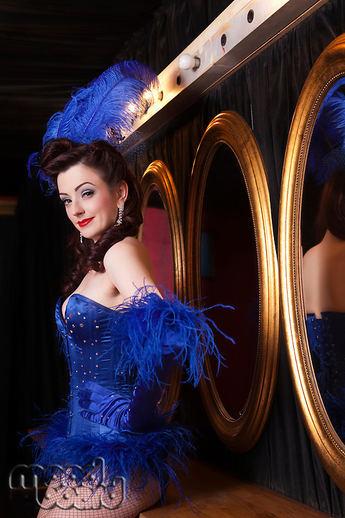 Showgirl standing by mirrors