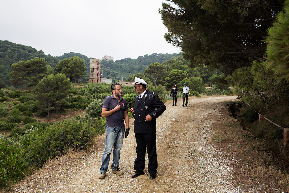 GORGONA, ITALY - 27 JUNE 2014: (L-R) Inmate Umberto Prinzi (43) chats with Giuseppe Picano, captain of the Penitentiary Police guard ship,  in Gorgona, Italy, on June 27th 2014.<br /> <br /> Gorgona is the smallest island of the Tuscan archipelago, located 18 miles west of Livorno, which became an experimental agricultural penal colony in 1869.<br /> <br /> The &ldquo;Frescobaldi per Gorgona&rdquo; project  provides inmates the opportunity to learn winemaking techniques and job skills under the supervision of the company&rsquo;s agronomists and winemakers, led by Vice President Lamberto Frescobaldi himself. Fifty inmates contributed to the production of Gorgona, a white wine made from Vermentino and Ansonica grapes planted on the island of Gorgona in the Tyrrhenian Sea, close to the Tuscan coast. The Frescobaldi family purchased a hectare of old vineyards and will expand with more vineyards in the upcoming months. Total production is only 2,700 bottles, but 1,000 of the bottles will reach the US market through Frescobaldi importer Folio Fine Wine Partners, in the Fall.<br /> <br /> Born in August 2012, the Gorgona initiative was financed by the Department of Penitentiary Administration and accomplished through the collaboration of the Gorgona Penitentiary's Directorate and Marchesi de&rsquo; Frescobaldi.