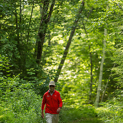 A man walks on a trail near Page Pond in Meredith, New Hampshire.