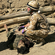 10th July 2007.Kajaki, Helmand Province, Afghanistan..Soldiers from 1st Battalion Royal Anglians and the Afghan National Army conduct operations against the Taliban in the Kajaki district of Helmand Province, Afghanistan on the 10th July 2007. After a long day of skirmishes with the Taliban an air strike was called on a compound thought to contain an enemy firing position. After the explosions the British and Afghan troops moved into the destroyed compound where they found 3 dead fighters and captured 2 more who were trapped in their collapsed bunker. The captured men both received medical treatment from the British and were given water by the Afghan soldiers they had been fighting only minutes before. A number of weapons were captured including Kalashnikov assault rifles, rocket propelled grenade launchers and war heads and a belt fed machine gun. The soldiers of 1 Royal Anglian have been fighting the Taliban in the area for more than 3 months; this constitutes their most successful capture of weapons and enemy fighters.