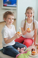 Portrait of siblings celebrating birthday with cup cakes