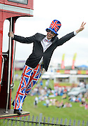 © Licensed to London News Pictures. 01/06/2012. Epsom , UK Robin Voogd hangs off the back of a bus wearing a union flag outfit. Ladies Day today 1st June 2012 at Epsom 2012 Investic Derby Festival. The Queen will attend tomorrow's race meet as part of the 60th Jubilee celebrations. Photo credit : Stephen Simpson/LNP