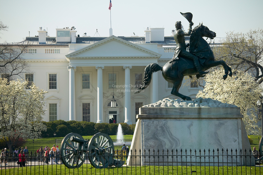 Statue of Andrew Jackson on horseback in Lafayette Square across from The White House, Washington DC USA with the Washington Monument in the distance and tourists crowing against the White House fence on Pennsylvania Avenue<br />