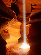 "A vibrant shaft of light illuminates a tumbleweed on the floor of Antelope Canyon in Page, Arizona. Antelope Canyon is a slot canyon that was carved by violent flash floods. Beams of light form only when the sun is nearly overhead, lighting up the blowing sand that fills the canyon, which is dozens of feet deep. The Navajo people call the canyon Tsé bighánílíní dóó Hazdistazí, which means ""the place where water runs through rocks."""
