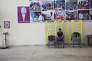 Un jeune élève du Bhiwani Boxing Club, dans un moment de pause. Derrière lui, images des personages importants pour l'école et à gauche la balance au-dessous d'une image du dieu Shiva - symbole de puissance et distruction mais aussi de force intérieure et bon augure