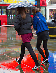 Two women make a dash through a wet Piccadilly Circus. As forecasters predicted, the rain arrives in London where Londoners and tourists go about their business. London, February 13 2018.