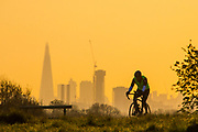 UNITED KINGDOM, London: 18 April 2018 A cyclist cycles past the London city skyline this morning in Richmond Park. Londoners will be enjoying the weather today as temperatures are set to reach a high of 25 degrees Celsius in the capital. Rick Findler / Story Picture Agency