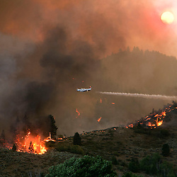 A plane dumps water on a set of trees while fighting the Elk fire near Pine, Idaho. Sunday August 11, 2013