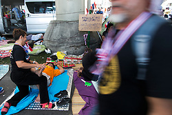 © Licensed to London News Pictures. 05/01/2014. A protestor gets a massage from one of the many vendors as a protestor walks past  during the third day of the 'Bangkok Shutdown' as anti-government protesters continue with their 'shutdown' of Bangkok.  Major intersections in the heart of the city have been blocked in their campaign to oust Prime Minister Yingluck Shinawatra and her government in Bangkok, Thailand. Photo credit : Asanka Brendon Ratnayake/LNP