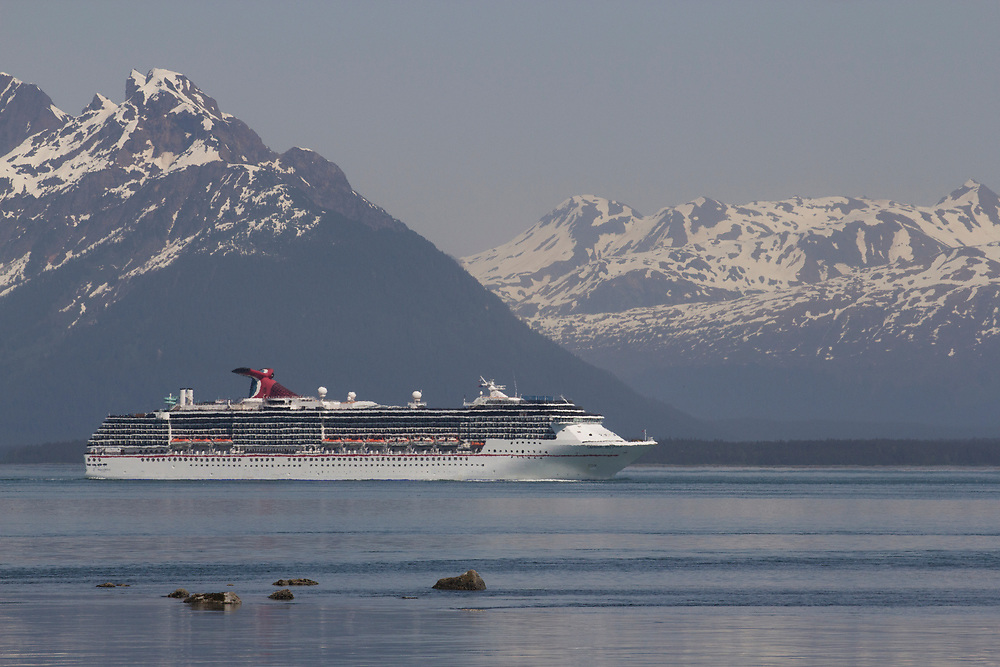 A cruise ship navigates Glacier Bay with Beartrack Mountain in the background.