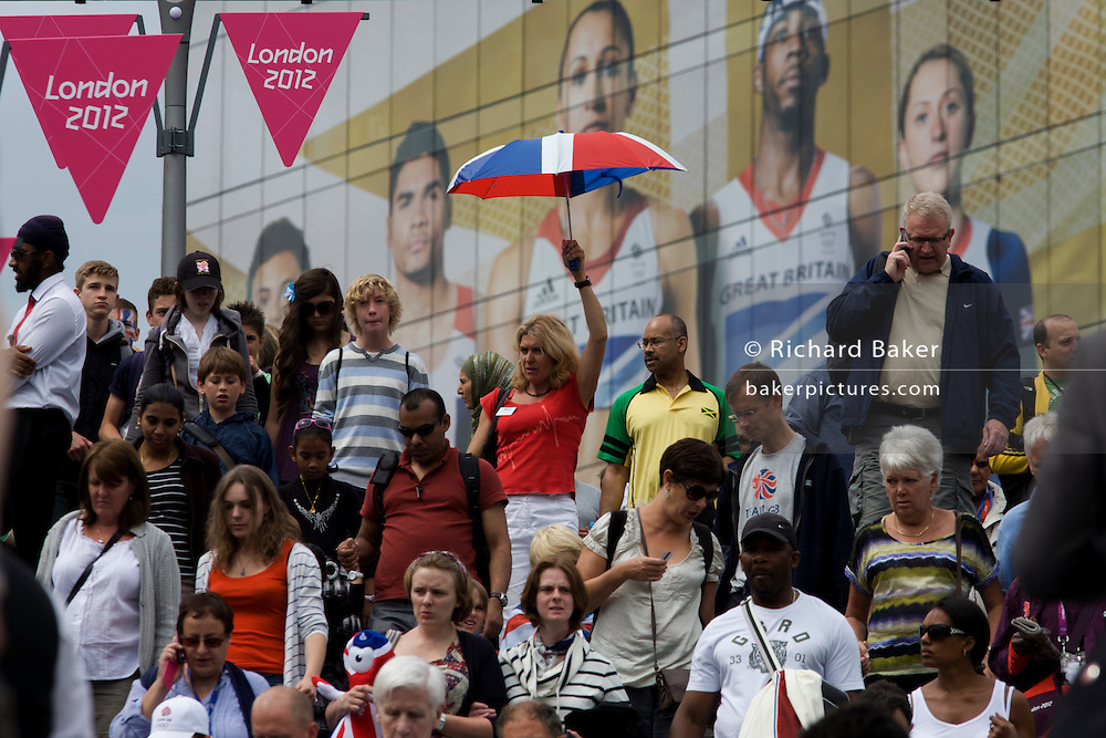 With giant presence of Team GB role-model athlete heroes behind them, spectator crowds descend steps at the Westfield City shopping complex, Stratford that leads to the Olympic Park during the London 2012 Olympics, the 30th Olympiad. The ad is for sports footwear brand Adidas and their 'Take the Stage' campaign including diver Tom Daley, gymnast Louis Smith and the darling of British athletics, heptathlete gold medallist Jessica Ennis. Situated on the fringe of the 2012 Olympic park, Westfield is Europe's largest urban shopping centre providing the main access to the Olympic park with a central 'street' giving 75% of Olympic visitors access to the main stadium so retail space...