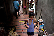 One of Seema Gupta's children plays in their shophouse in Ghaziabad, Uttar Pradesh, India. Seema Gupta, aged 34 (unseen), had a tubectomy done on 9 June 2011 for family planning while her husband, Ramesh Chandra Gupta, aged 38 (unseen), wasn't aware of the option and benefits of non-scalpel vasectomy (NSV). They run a roadside sweets shop at the front of their house and chose to have a family planning surgery done as they did not want to compromise the quality of life for their two children. While Ramesh wanted only 1 child, both his mother and Seema pushed for a 2nd child. Photo by Suzanne Lee / Panos London