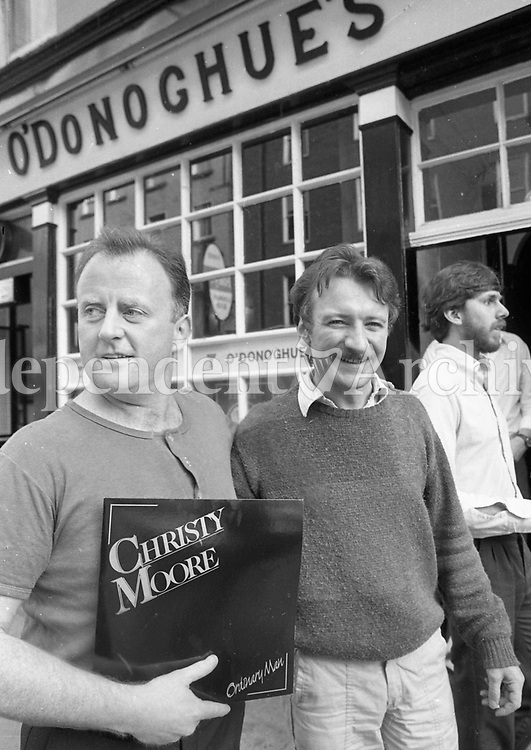 Singer Christy Moore being congratulated by folk singer Donal Lunny at the launch of his record Ordinary Man, in O'Donoghues pub in Merrion Row, Dublin, 29/07/1985.  <br /> (Part of the Independent Newspapers Ireland/NLI Collection).