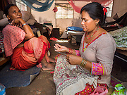 02 AUGUST 2015 - BHAKTAPUR, NEPAL:  Women make tourist curios in their tent in a small Internal Displaced Person (IDP) camp at Durbar Square in Bhaktapur for people left homeless by the Nepal earthquake. The Nepal Earthquake on April 25, 2015, (also known as the Gorkha earthquake) killed more than 9,000 people and injured more than 23,000. It had a magnitude of 7.8. The epicenter was east of the district of Lamjung, and its hypocenter was at a depth of approximately 15km (9.3mi). It was the worst natural disaster to strike Nepal since the 1934 Nepal–Bihar earthquake. The earthquake triggered an avalanche on Mount Everest, killing at least 19. The earthquake also set off an avalanche in the Langtang valley, where 250 people were reported missing. Hundreds of thousands of people were made homeless with entire villages flattened across many districts of the country. Centuries-old buildings were destroyed at UNESCO World Heritage sites in the Kathmandu Valley, including some at the Kathmandu Durbar Square, the Patan Durbar Squar, the Bhaktapur Durbar Square, the Changu Narayan Temple and the Swayambhunath Stupa. Geophysicists and other experts had warned for decades that Nepal was vulnerable to a deadly earthquake, particularly because of its geology, urbanization, and architecture.      PHOTO BY JACK KURTZ