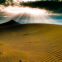 Sun shining on sand dunes