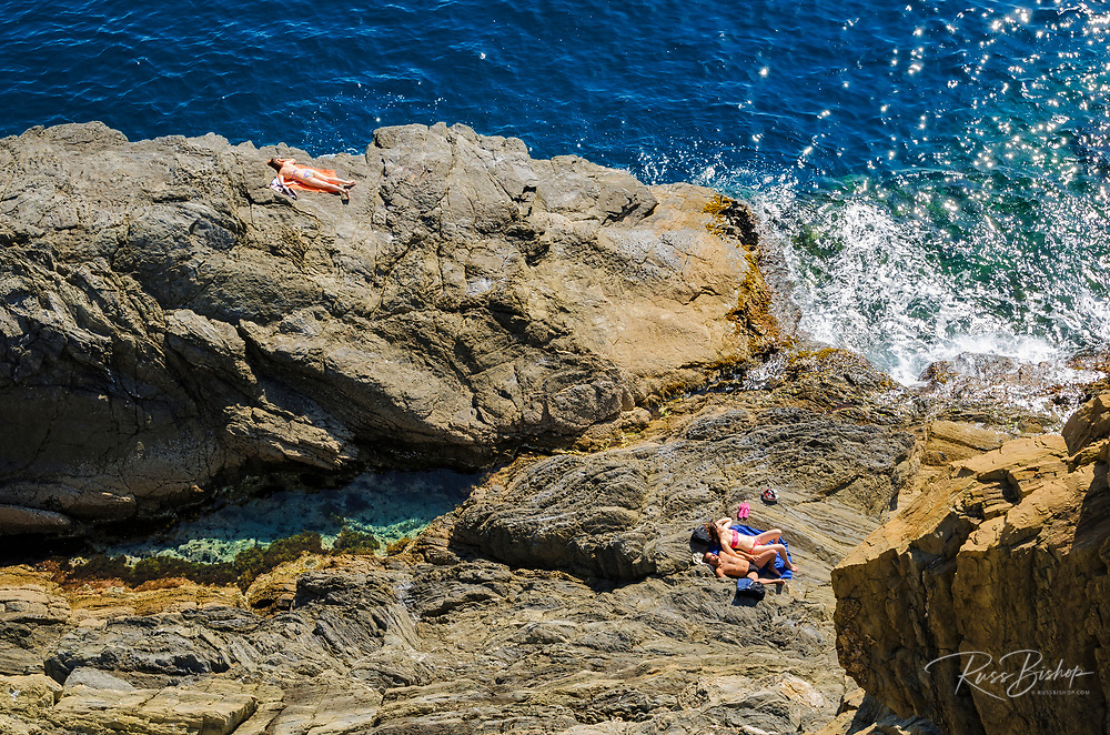 Sunbathers below the Via dell'Amore, Riomaggiore, Cinque Terre, Liguria, Italy