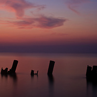 Remains of an old pier and morning twilight over the Delaware Bay, Port Mahon, DE