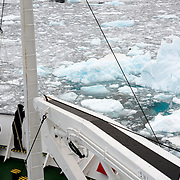 "Passengers stand on the bow of an ice-strengthened cruise ship as it navigates the Lemaire Channel with the surface of the water covered with sheet ice and brash ice. The Lemaire Channel is sometimes referred to as ""Kodak Gap"" in a nod to its famously scenic views."
