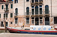 A woman wearing yellow walks below Venetian architecture along a quiet canal with her shopping cart, past a blue and red boat in Venice, Italy