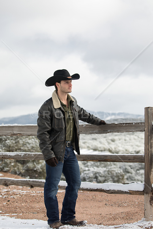 cowboy by a spilt rail fence in Winter