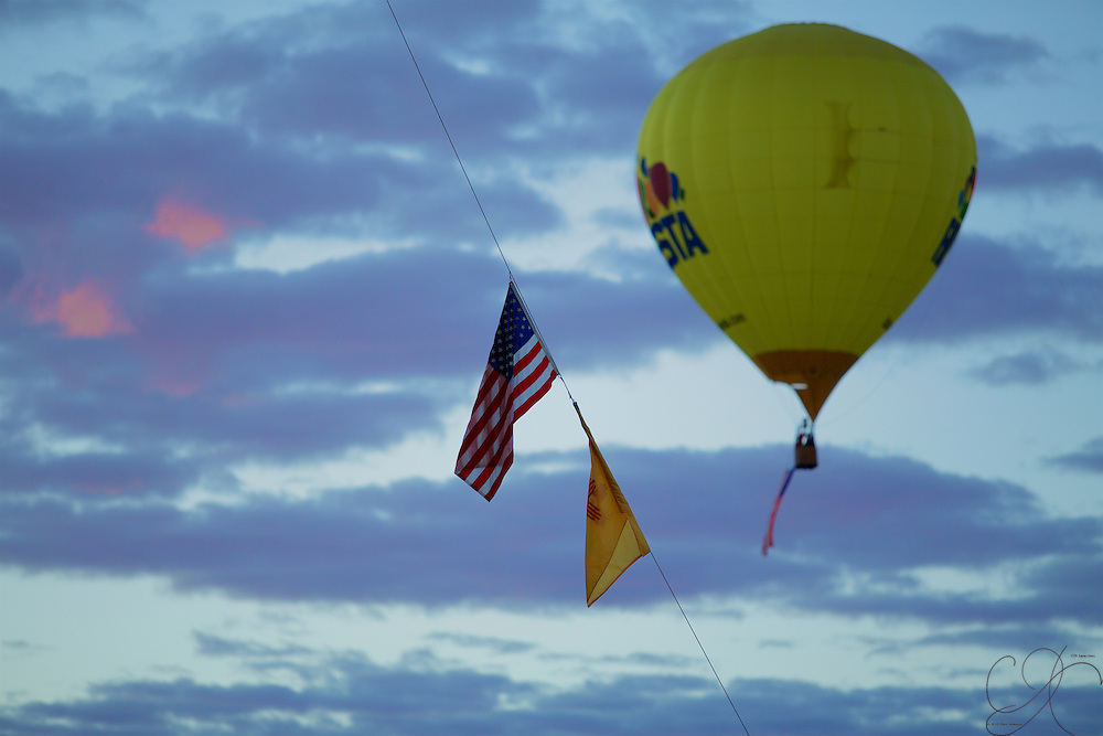 Old glory is flown over the field from the Fiesta balloon while other local pilots proudly fly the colors from their own balloons.