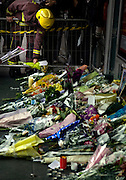 A Fire Fighter is laying flowers at Kings Cross station on Saturday July 9, 2005 in London , England. Three subway trains and one bus were bombed two days earlier on Thursday Juli 7.