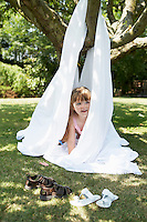 Young girl in back yard peeking out of tent made of sheet