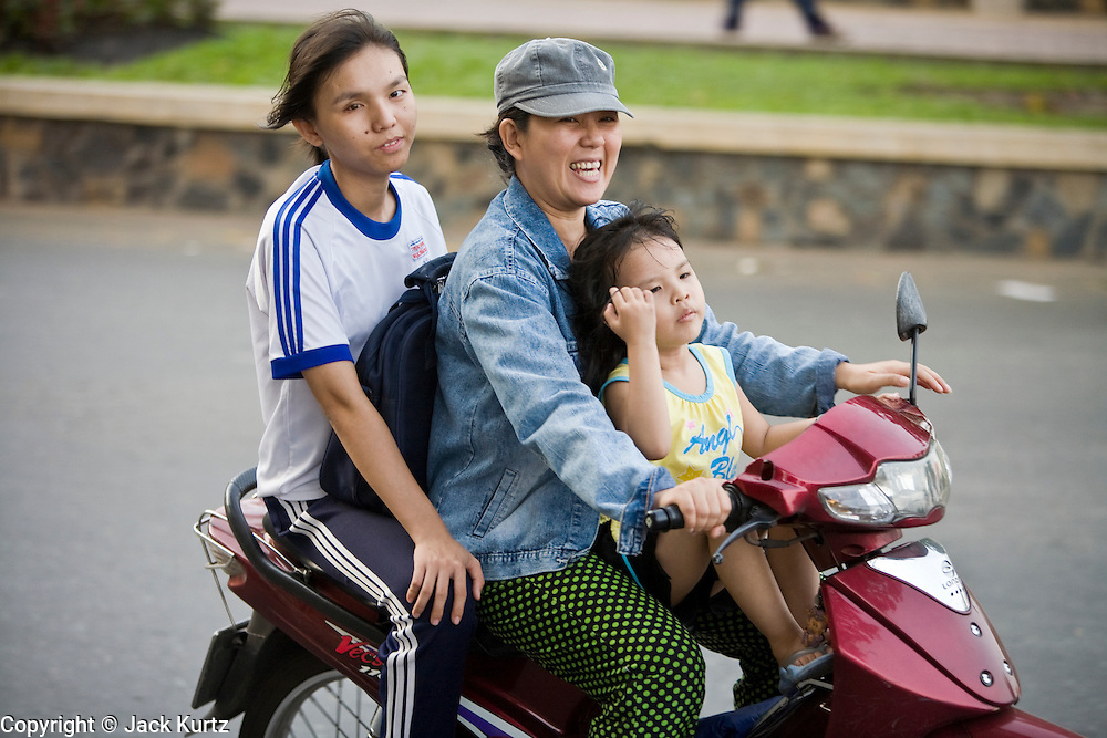 08 MARCH 2006 - HO CHI MINH CITY, VIETNAM: A family on a motorscooter in Ho Chi Minh City, Vietnam. HCMC is still widely known as Saigon. Rapid economic development in southern Vietnam has allowed many people who used to rely on bicycles for transportation to upgrade to motorscooters and motorcycles.   PHOTO BY JACK KURTZ