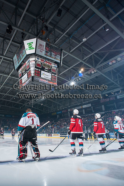 KELOWNA, CANADA - JANUARY 10: Madison Bowey #4 and Josh Morrissey #27 of Kelowna Rockets stand on the blue line in their Team Canada World Junior Hockey Championship jerseys and watch replay video during a ceremony on home ice on January 10, 2015 at Prospera Place in Kelowna, British Columbia, Canada.  (Photo by Marissa Baecker/Shoot the Breeze)  *** Local Caption *** Madison Bowey; Josh Morrissey;